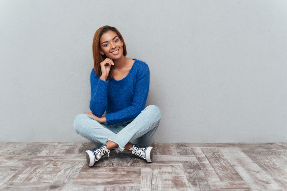 Smiling african woman in sweater and jeans sitting on the wooden floor in studio and holding one hand near the face as well as looking at camera. Isolated gray background