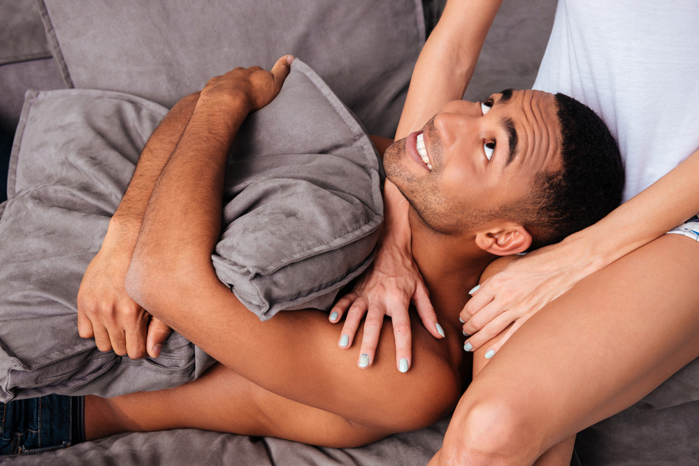 Smiling african young man lying on sofa with his girlfriend at home