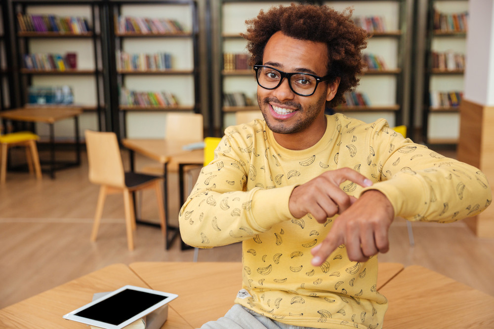 Smiling african young man using tablet and asking about the time in library