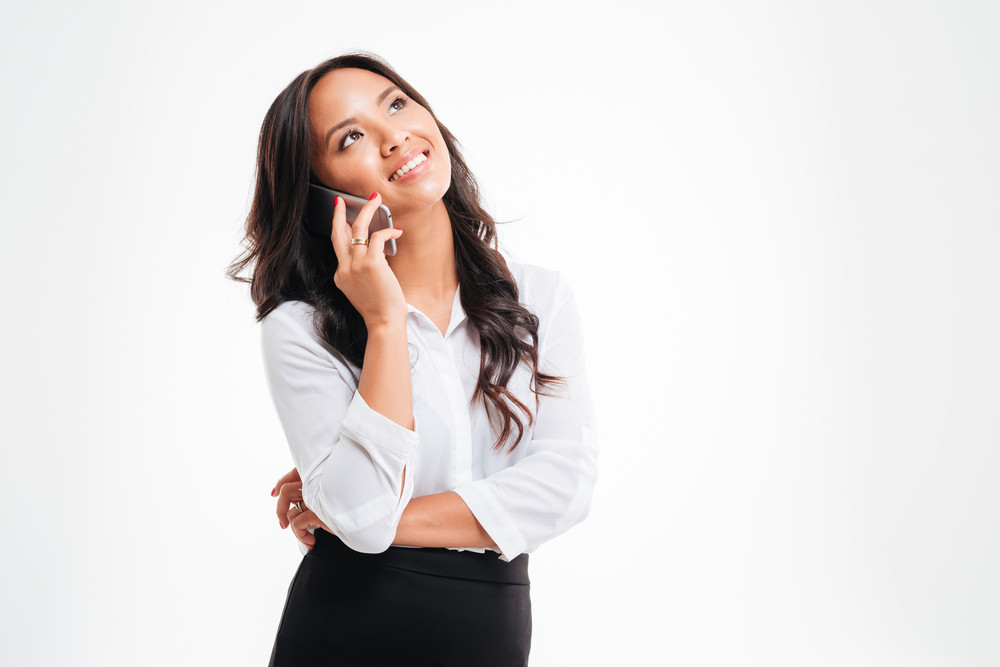 Smiling asian businesswoman talking on the phone isolated on a white background
