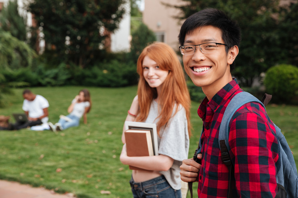 Smiling asian young man student with backpack walking with her girlfriend outdoors