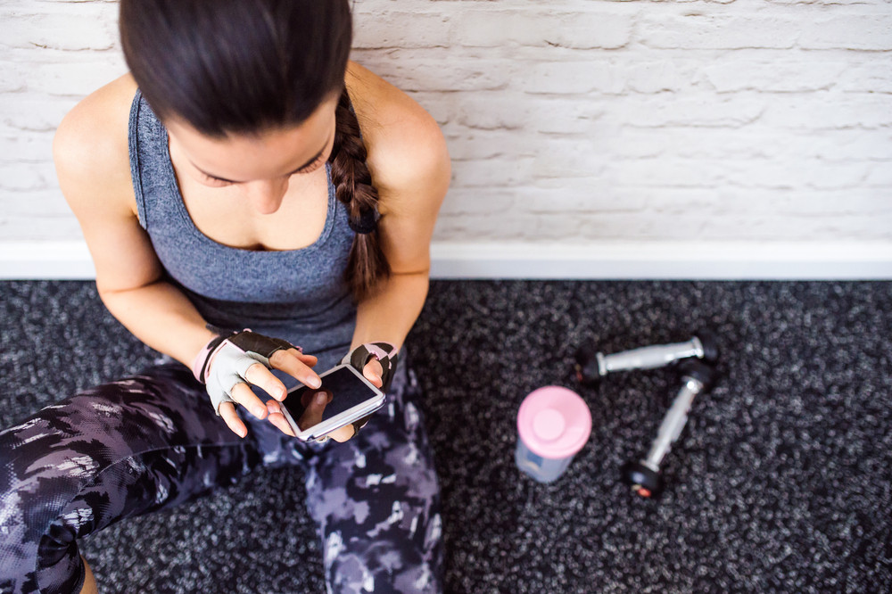 Smiling attractive fit woman in gym sitting on a floor holding smart phone against white brick wall, water bottle, weights