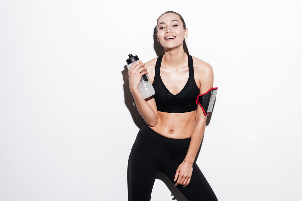 Smiling attractive young fitness woman with armband and bottle of water over white background