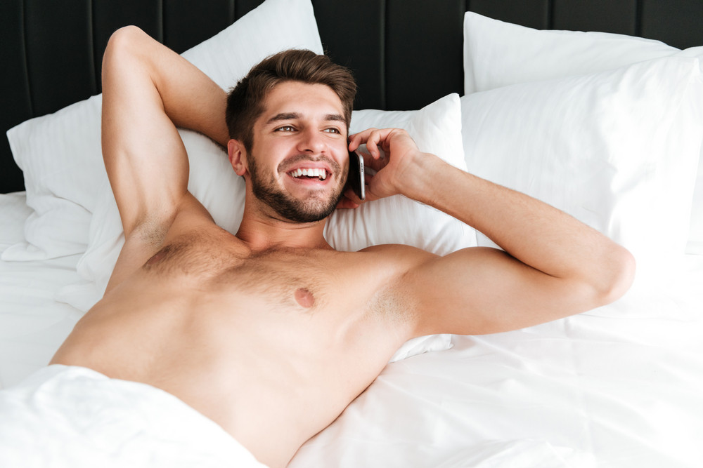 Smiling attractive young man lying and talking on cell phone in bed