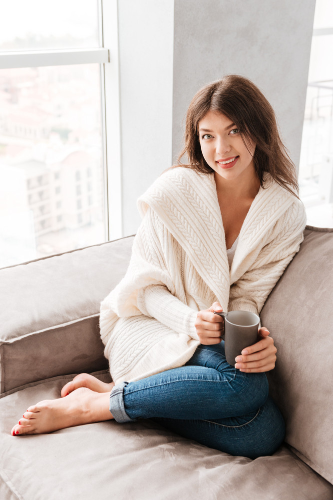 Smiling attractive young woman drinking coffee on sofa at home