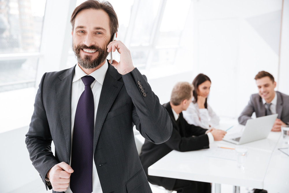 Smiling Bearded Business man talking at phone in office with colleagues on background