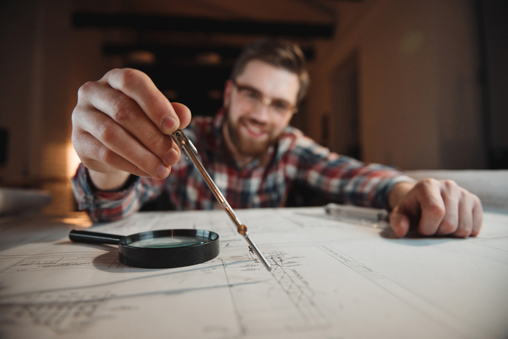 Smiling bearded man holding compass over graph on desk, focus on compass