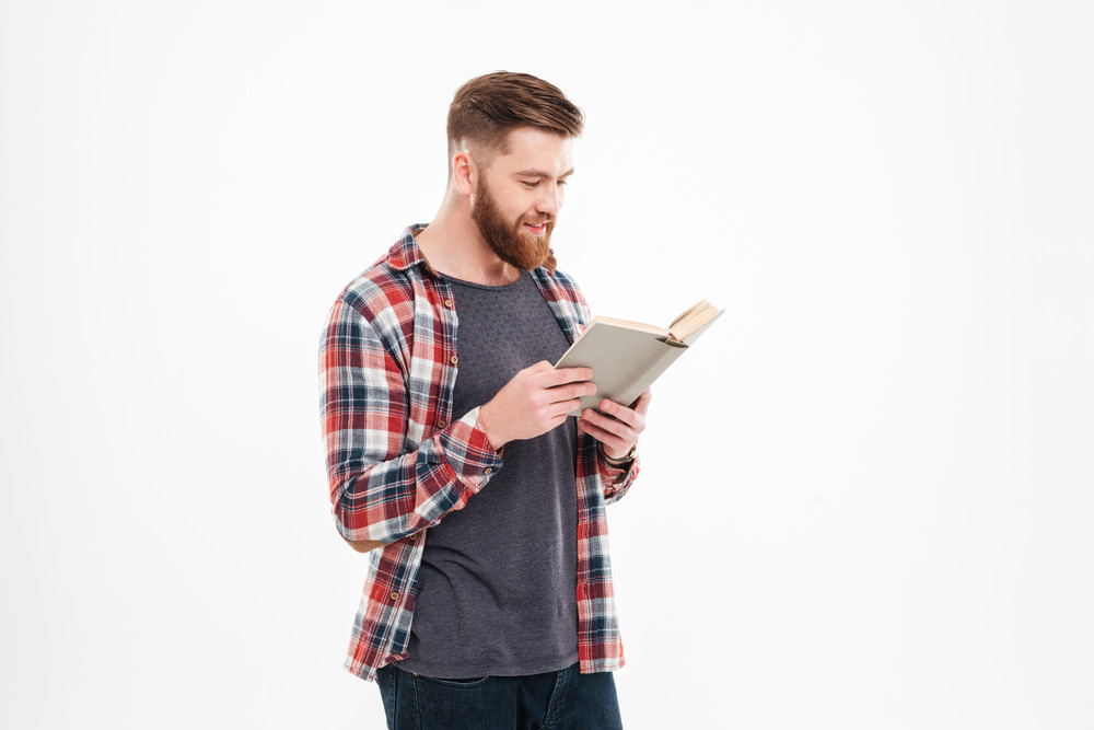 Smiling bearded man in plaid shirt standing and reading book isolated on a white background