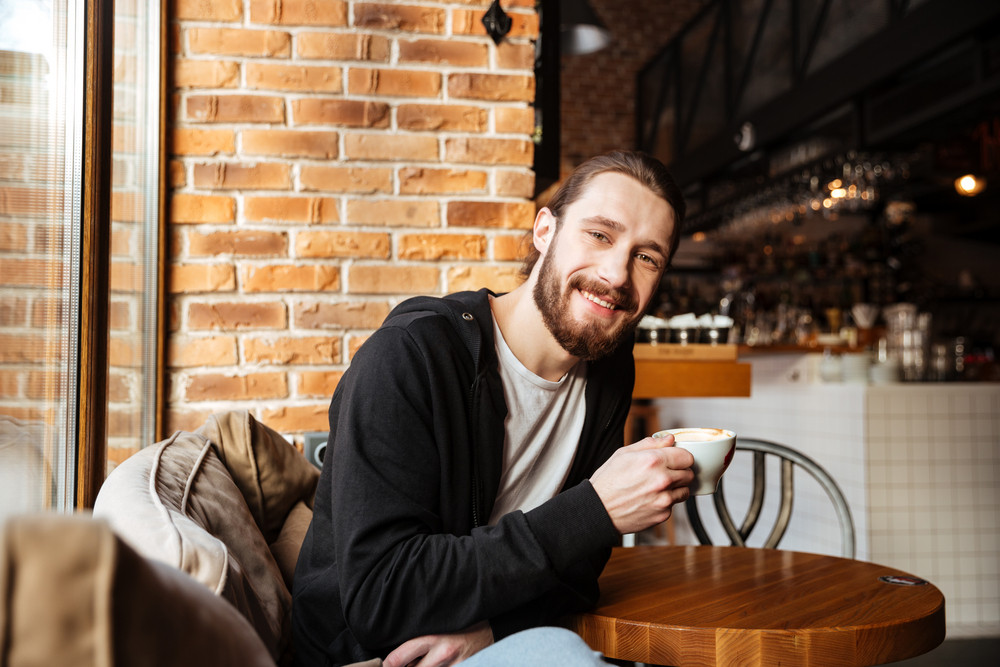 Smiling Bearded man sitting by the table in cafe with cup of coffee and looking at camera