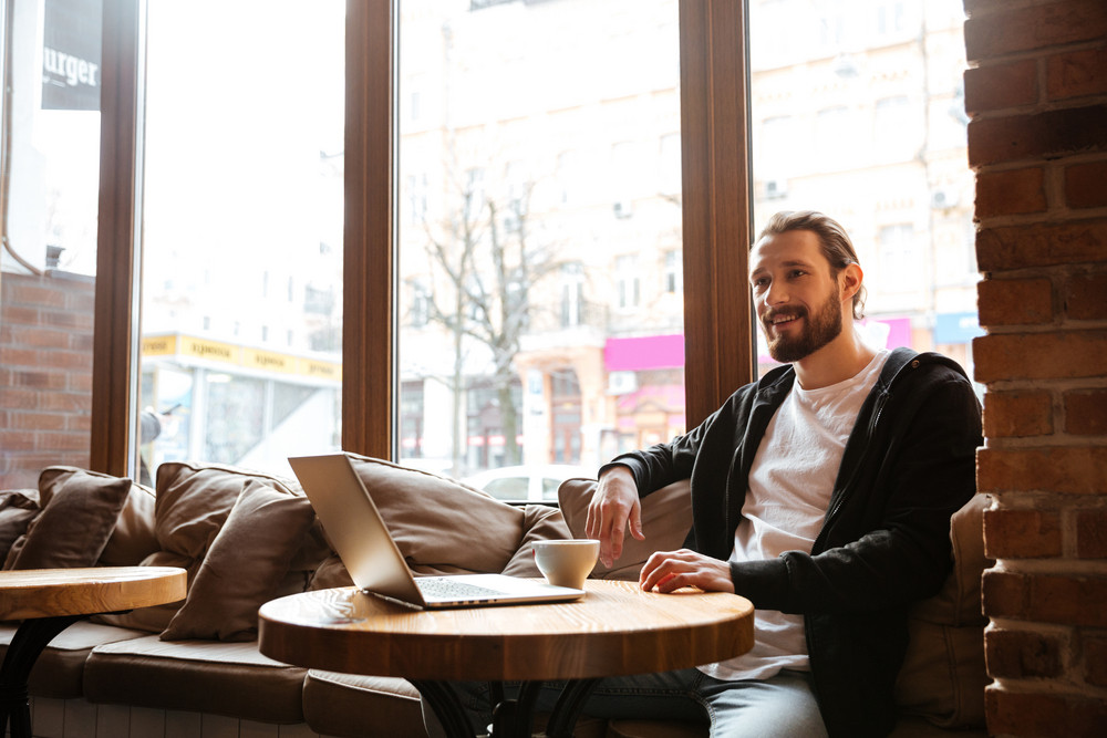 Smiling Bearded man sitting by the table with laptop computer with window on background