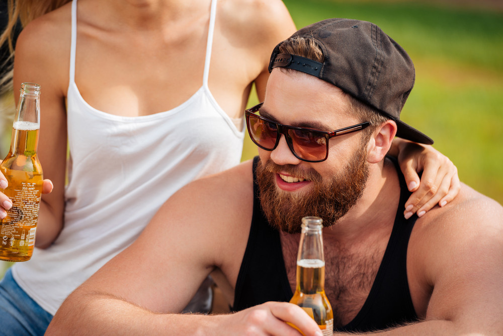Smiling bearded young man in cap sitting and drinking beer with his girlfriend outdoors