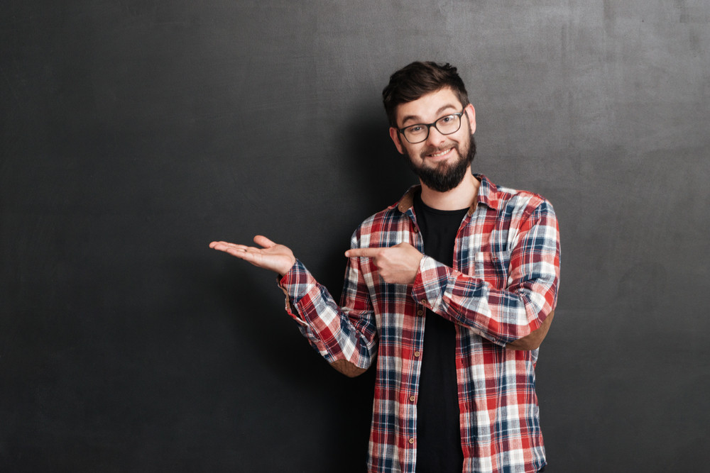 Smiling bearded young man in glasses holding copyspace on palm and pointing on it over grey background