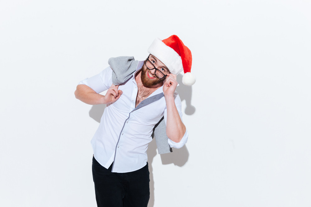 Smiling bearded young man in santa claus hat and glasses standing over white background