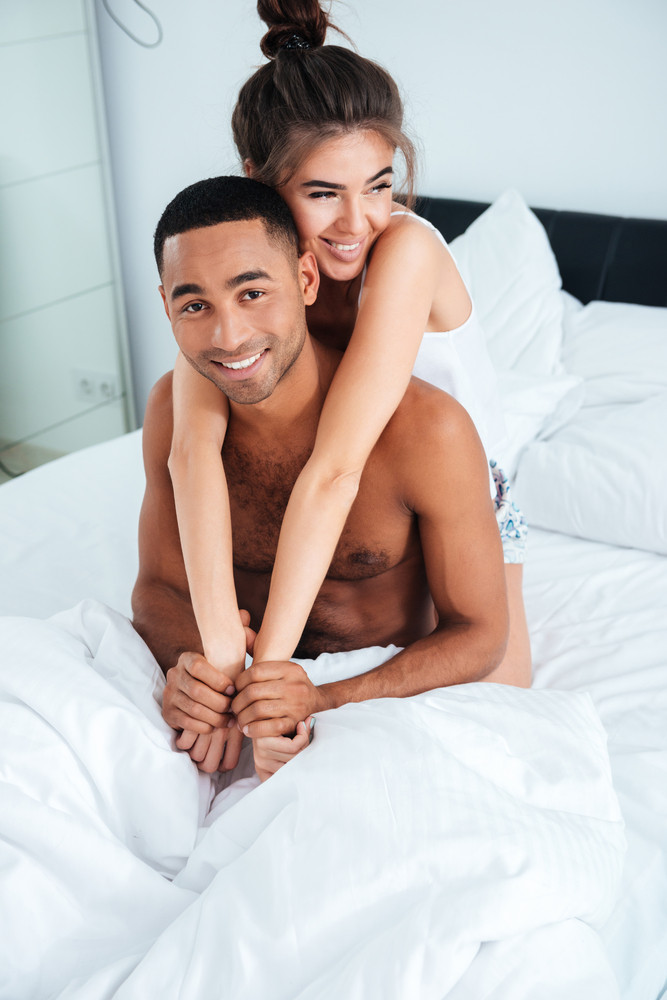 Smiling beautiful young couple sitting and embracing on bed at home