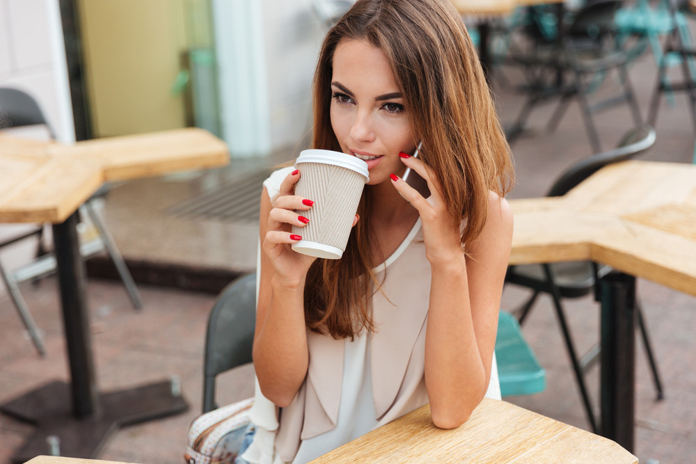 Smiling beautiful young woman drinking coffee and talking on cell phone while sitting in cafe