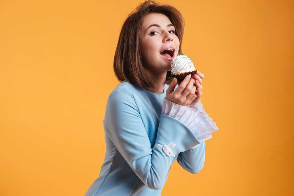 Smiling beautiful young woman holding and biting cupcake over yellow background