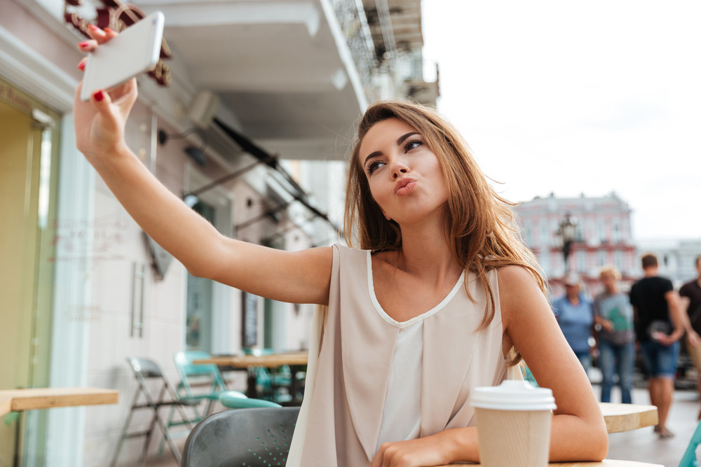 Smiling beautiful young woman taking selfie with smartphone sitting in cafe