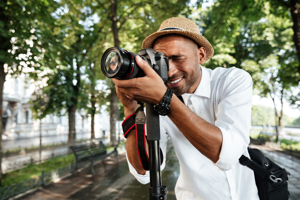 Smiling black man in park with camera