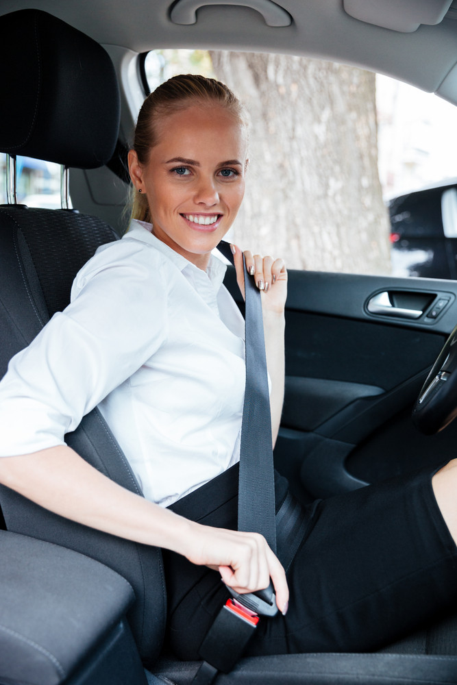 Smiling blonde business woman sitting in car and putting on her seat belt