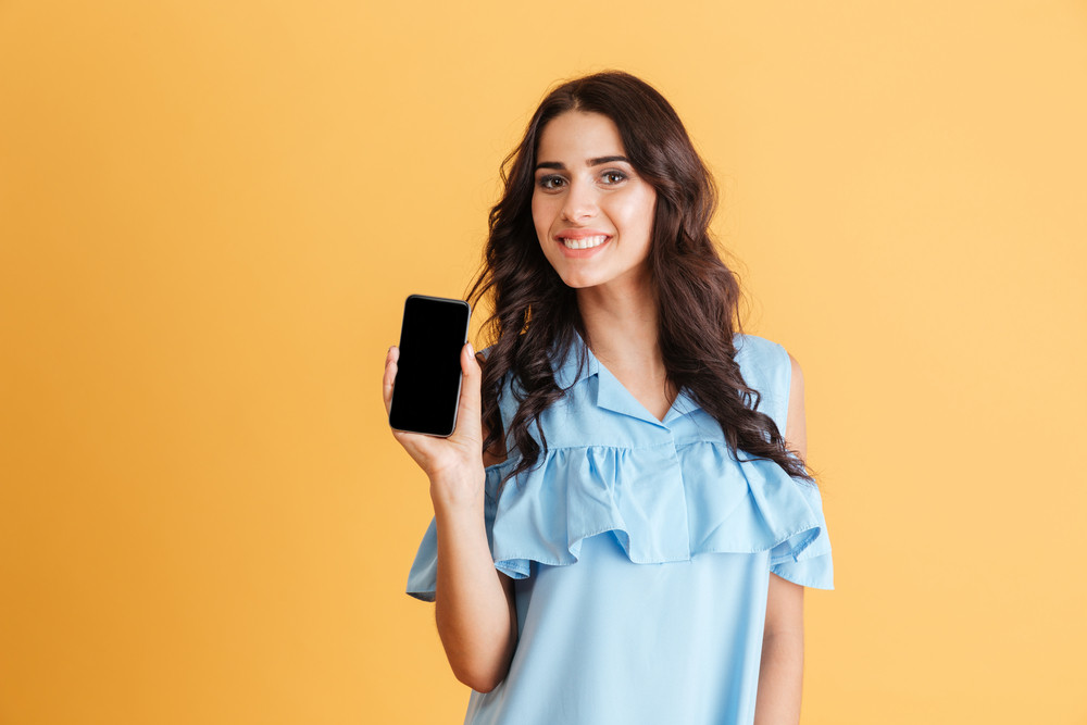 Smiling brunette woman in blue dress showing blank smartphone screen isolated on a orange background