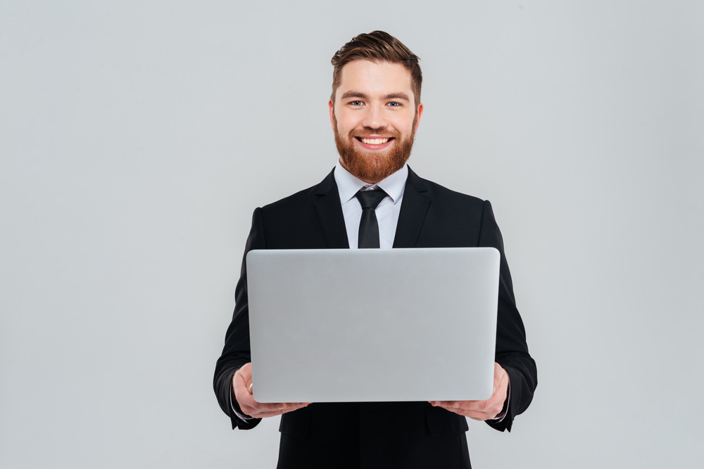 Smiling business man in black suit holding laptop and looking at camera. Isolated gray background