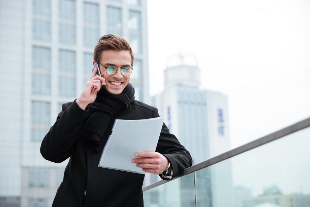 Smiling Business man in glasses and warm clothes talking at phone and reading documents outdoors