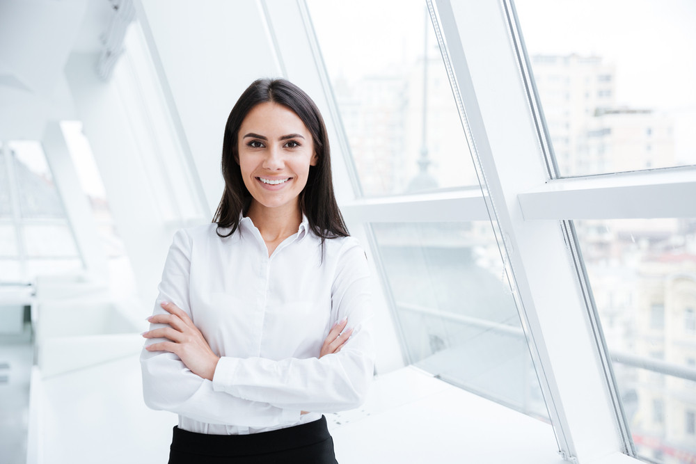 Smiling Business woman standing near the window in office with arms crossed and looking ar camera