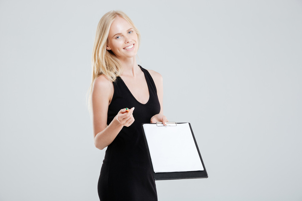 Smiling businesswoman showing blank clipboard and pointing at camera isolated on a white background