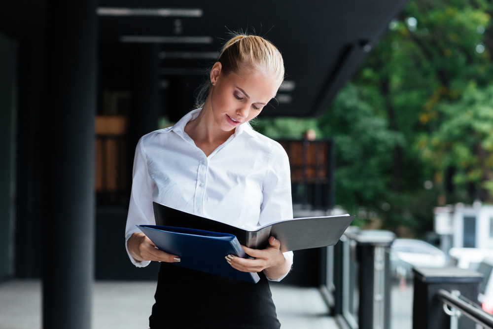 Smiling businesswoman standing with folders outside