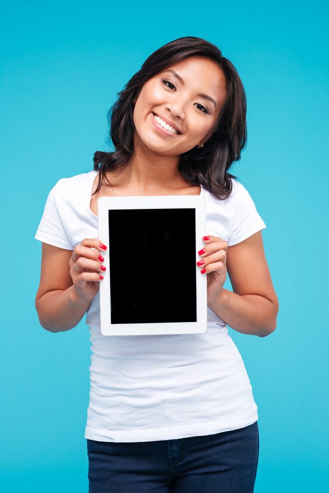 Smiling casual asian woman showing blank tablet computer screen isolated on a blue background