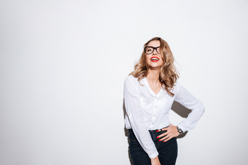 Smiling casual woman in eyeglasses standing and posing with hand on hips on white background