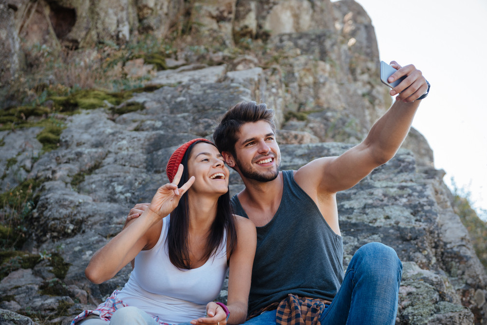 Smiling couple make selfie and sitting on rock