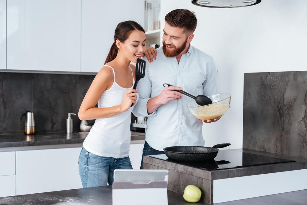 Smiling couple prepared cake near the stove.