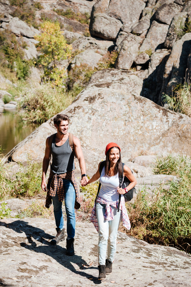 Smiling couple walking with backpacks over mountains together