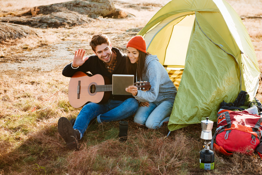 Smiling couple with guitar near the tent with tablet