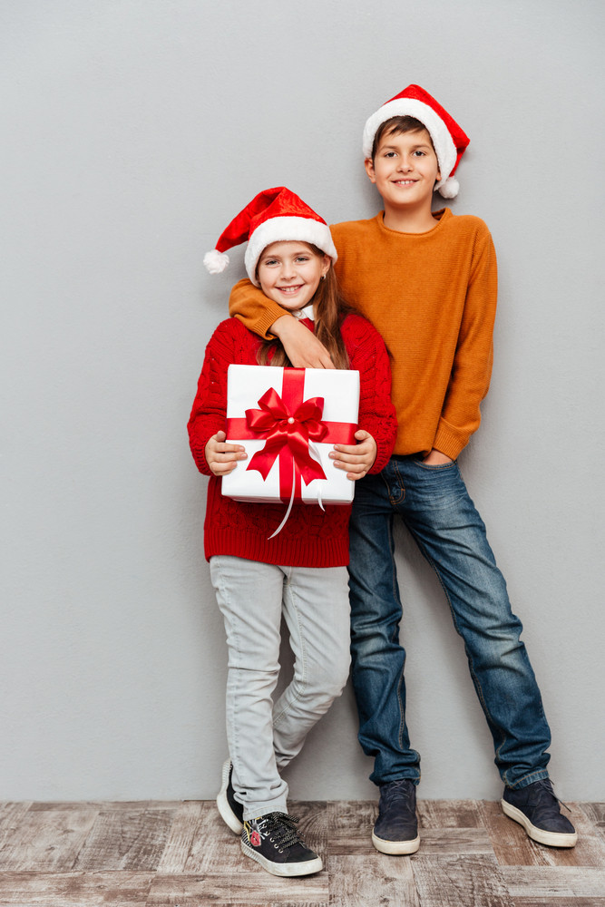 Smiling cute children in santa claus hats with gift box