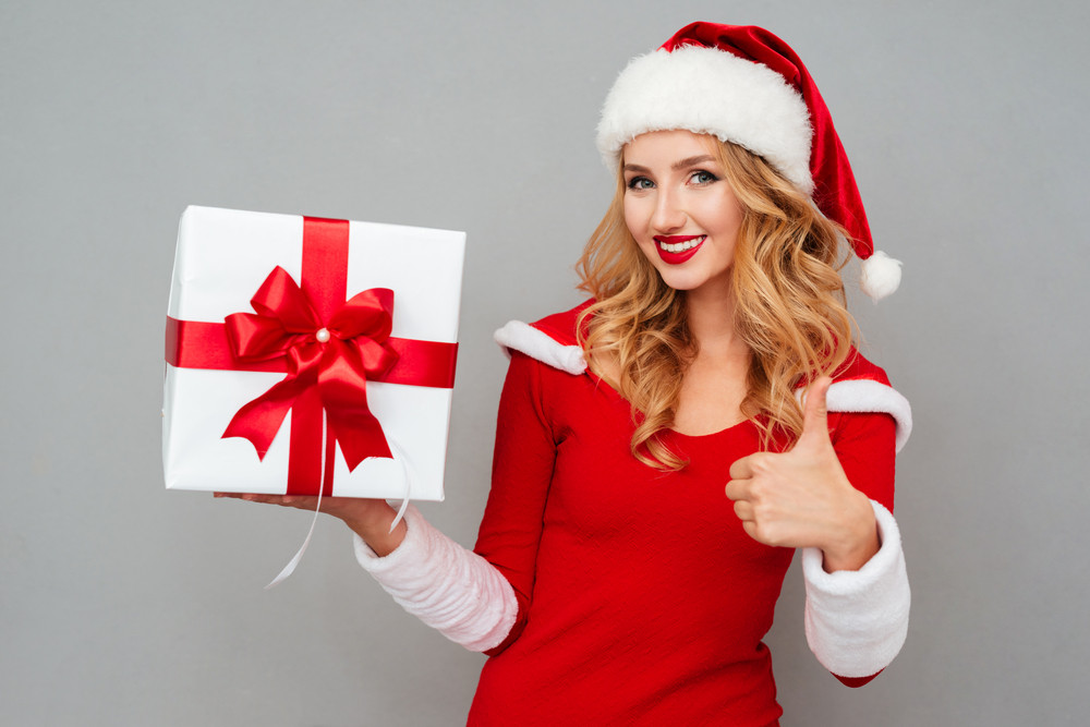 Smiling cute girl in red christmas outfit holding big gift box and showing thumbs up gesture isolated on the gray background