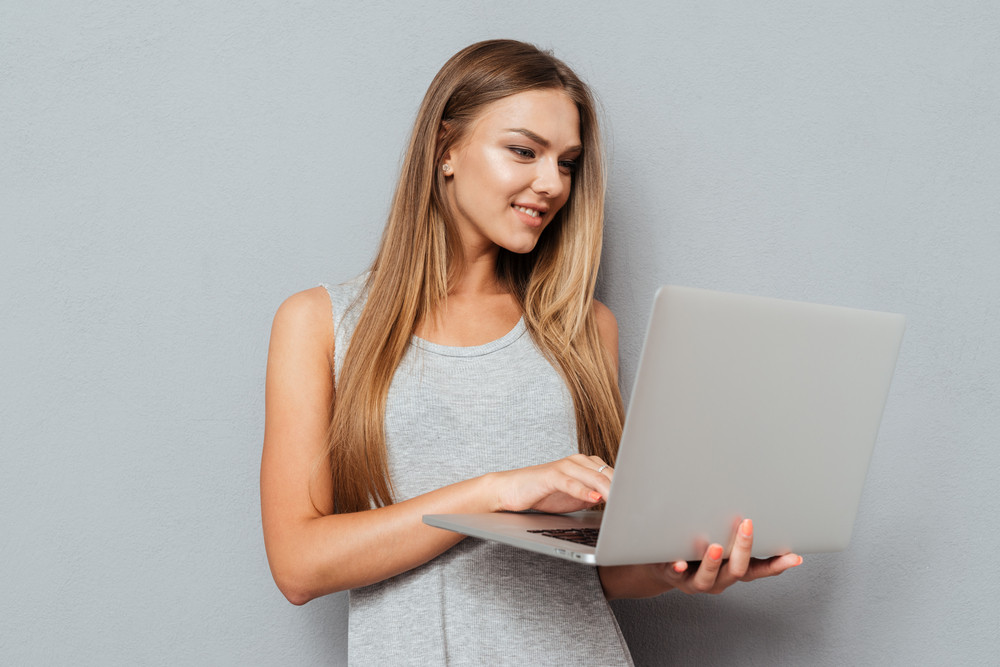 Smiling cute girl standing and using laptop over gray background