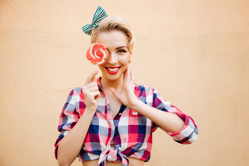 Smiling cute pin up girl cover her eye with lollipop over pink background