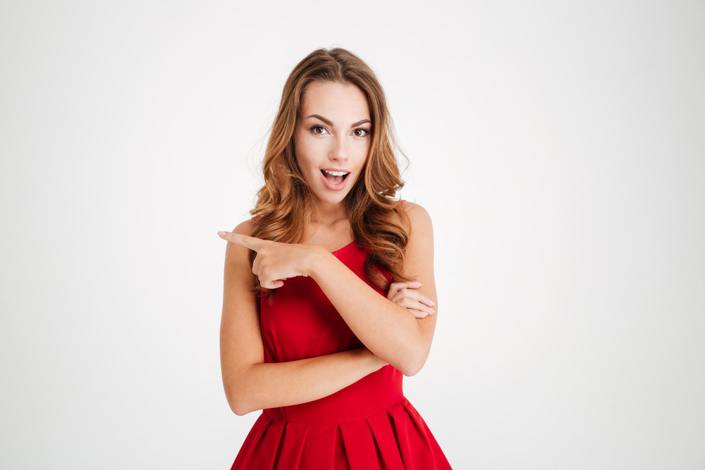 Smiling cute young woman standing and pointing away over white background