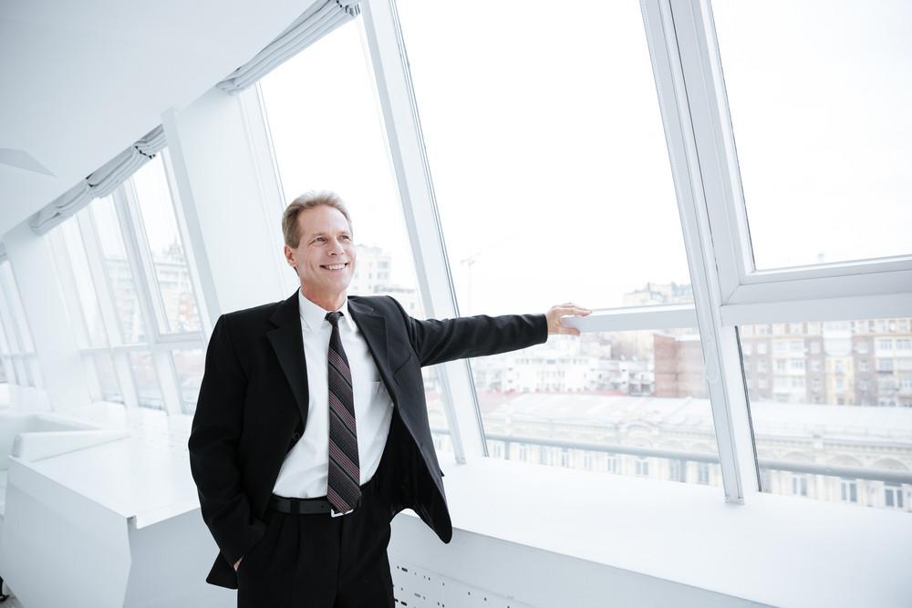 Smiling Elderly business man standing near the window in office