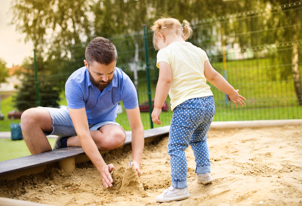 Smiling father and his little daughter playing on playground.