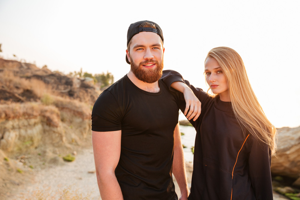 Smiling fitness couple standing at the beach together wearing sports uniform