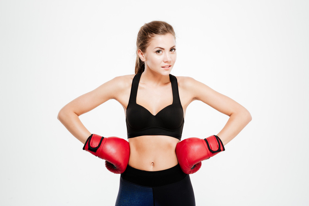Smiling fitness woman in boxing gloves over white background
