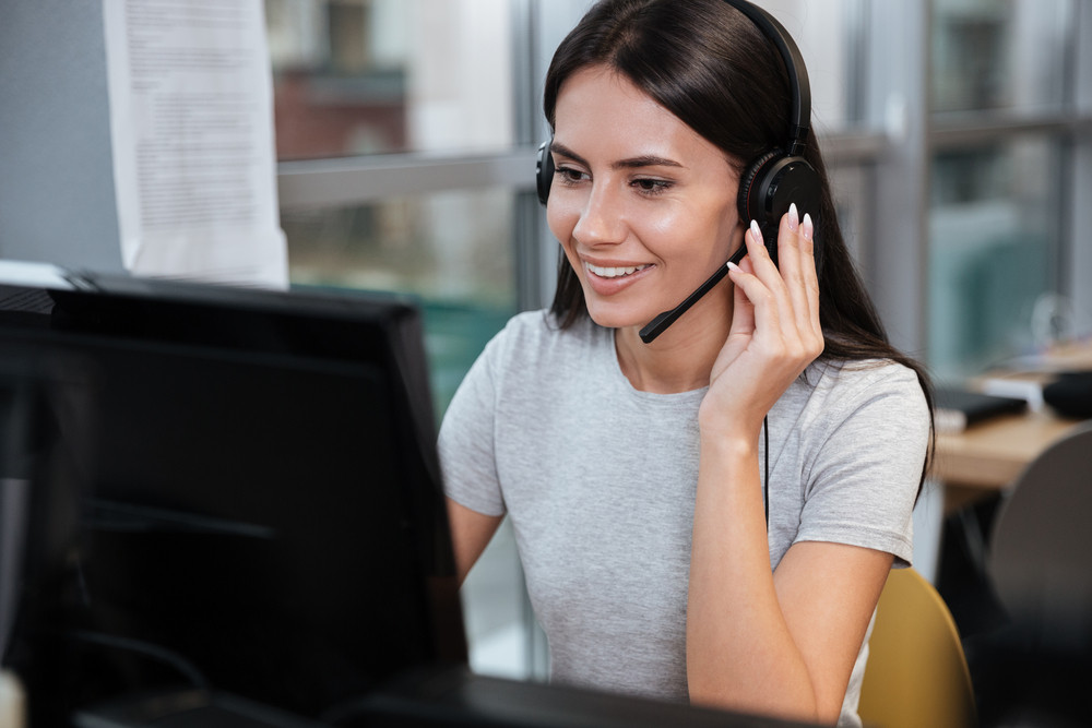 Smiling Girl in t-shirt sitting by the computer in headphone in office. Call center
