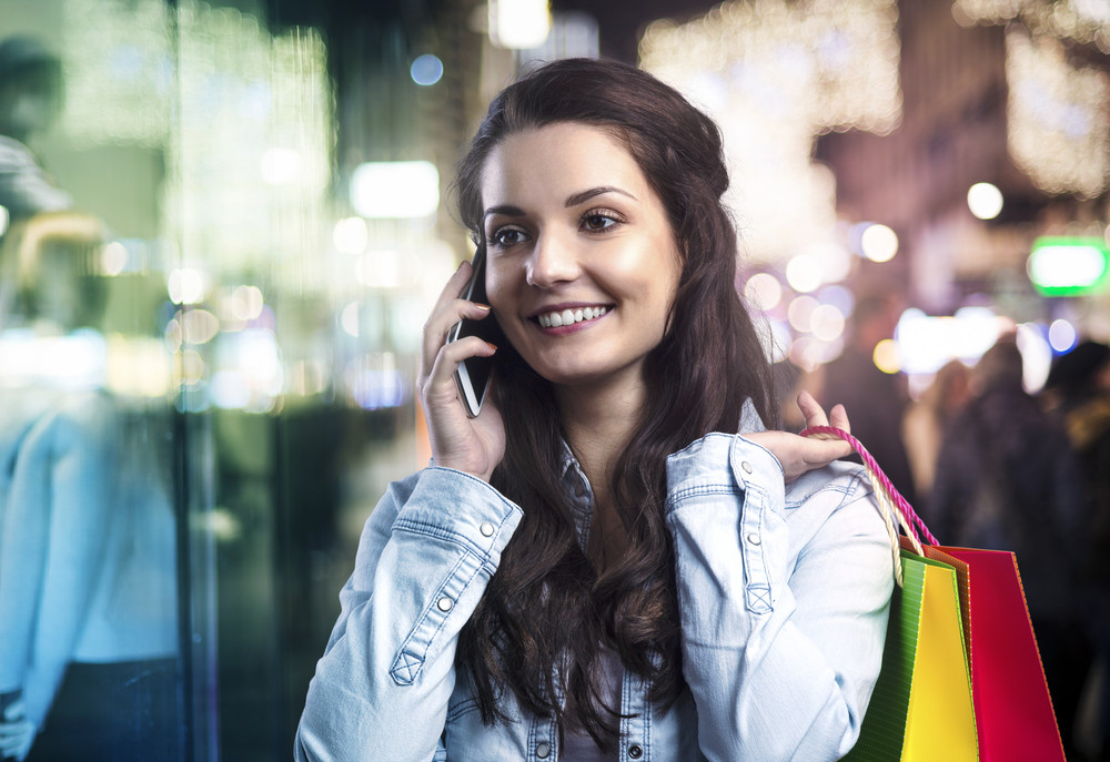 Smiling girl with shopping bags and her smart phone in a mall