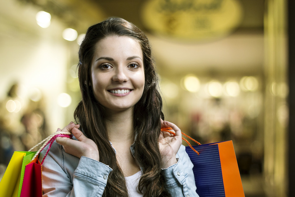 Smiling girl with shopping bags in a mall