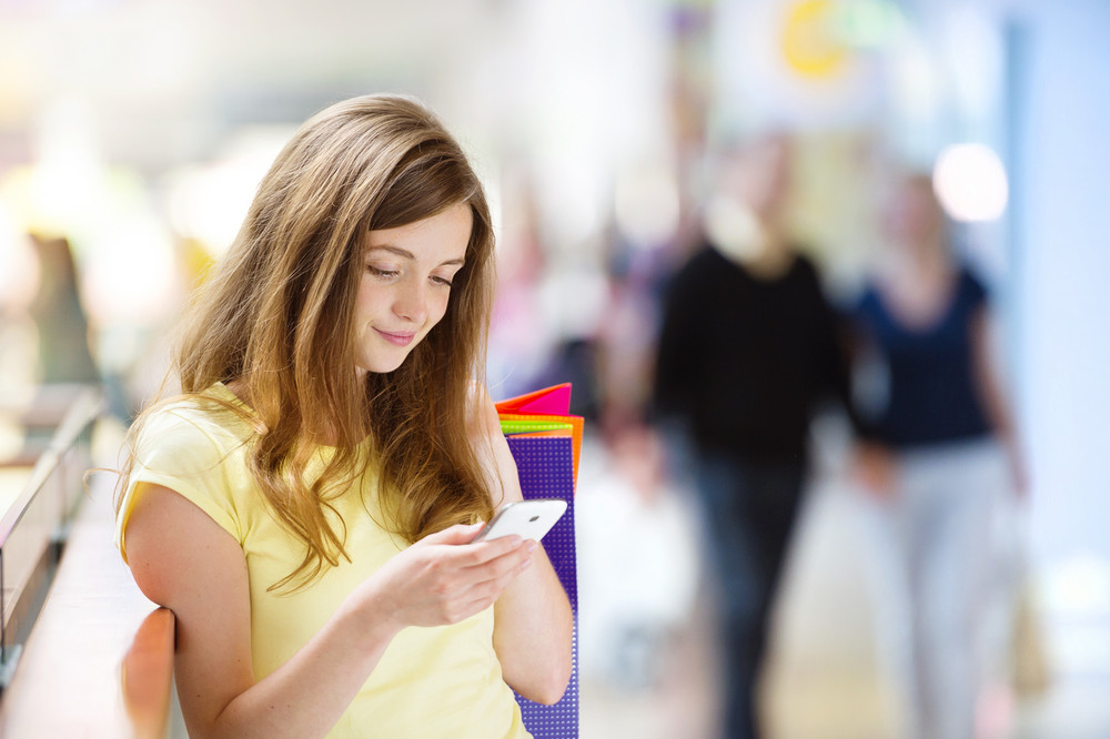Smiling girl with smartphone in shopping centre