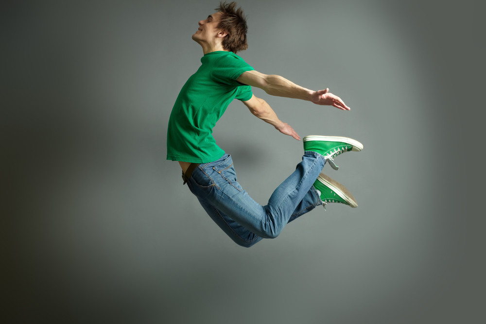 Smiling guy jumping high holding hands behind