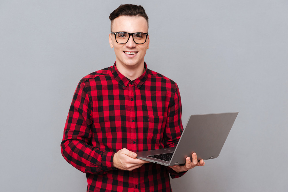 Smiling handsome Hipster holding laptop in hands and looking at camera. Isolated gray background